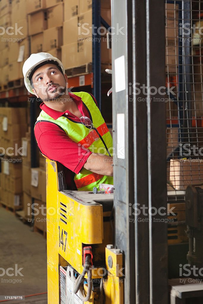 Warehouse worker operating forklift vehicle lifting packages and boxes stock photo