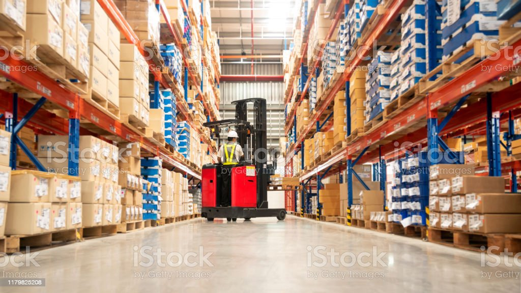 Warehouse Worker Worker in forklift-truck loading packed goods in huge distribution warehouse with high shelves. Aisle Stock Photo