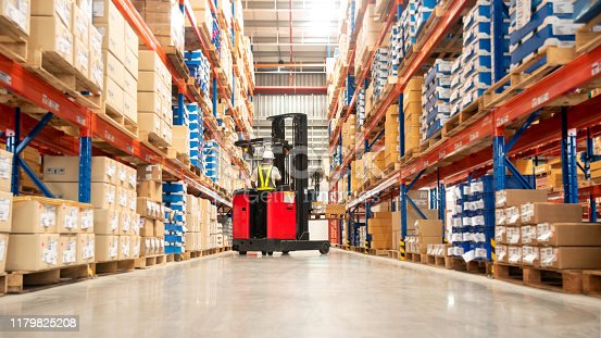 Worker in forklift-truck loading packed goods in huge distribution warehouse with high shelves.
