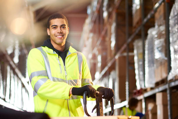 warehouse worker portrait a male warehouse worker smiles to camera . In the background a female colleague is checking some pallets. reflective clothing stock pictures, royalty-free photos & images
