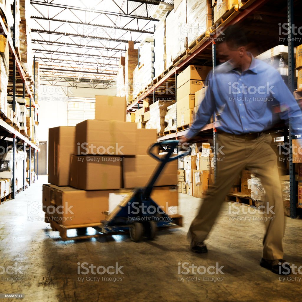 Warehouse Worker Pulling Dolly royalty-free stock photo