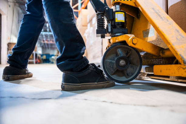 A warehouse worker runs over his toe with a pallet jack. A warehouse worker runs over his toe with a pallet jack. The pallet jack is actually resting on his toe. This is a common injury in industrial warehouses and manufacturing plants. pallet jack stock pictures, royalty-free photos & images