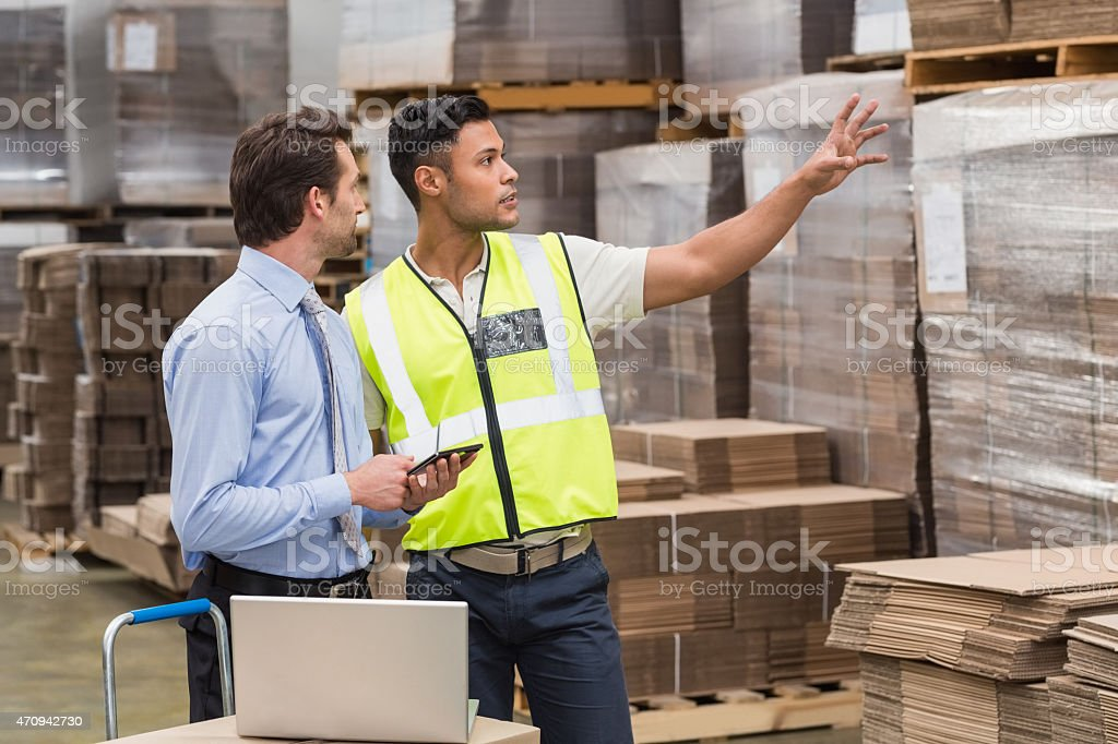 Warehouse worker showing something to his manager stock photo