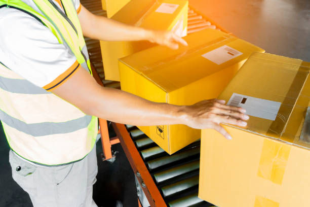 Warehouse worker sorting parcels package boxes on conveyor belt Warehouse worker sorting parcels package boxes on conveyor belt at distribution warehouse. warehouse industry delivery and transport. distribution center stock pictures, royalty-free photos & images