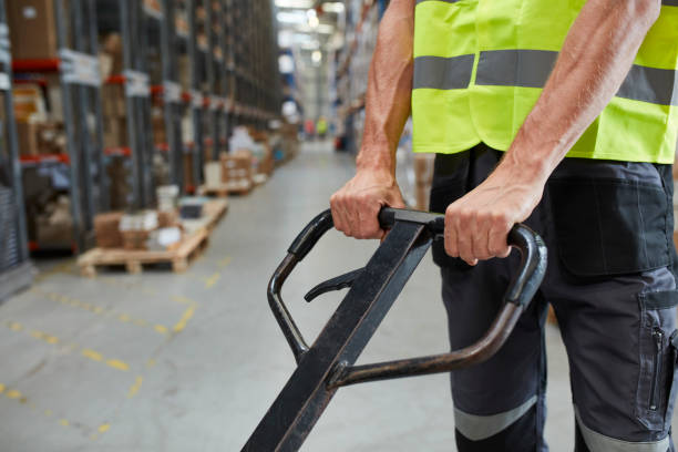 Warehouse worker standing among shelves with handcart Male worker distributing cardboard boxes in a warehouse. Close up pallet jack stock pictures, royalty-free photos & images