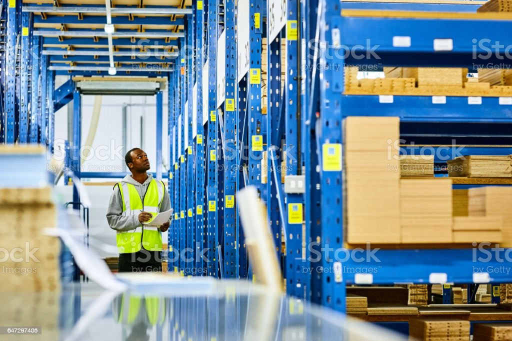 Warehouse worker taking inventory of products stock photo