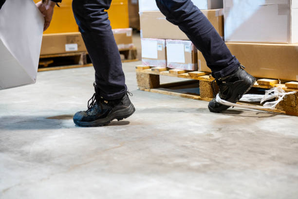A warehouse worker tripping and falling beside a pallet stock photo