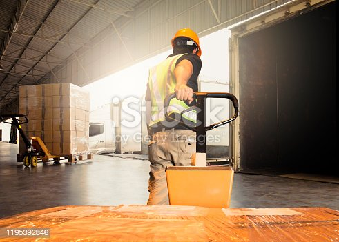 Warehouse worker unloading pallet shipment goods into a truck container, warehouse industry freight, logistics and transport.
