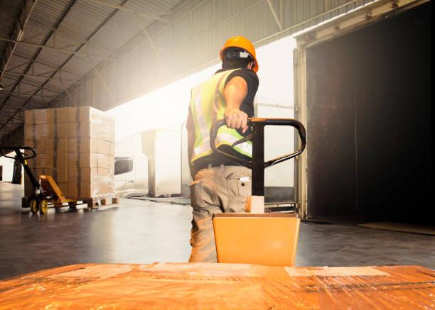 warehouse worker unloading pallet shipment goods into a truck container - caricare attività foto e immagini stock