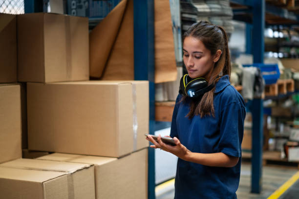 Warehouse worker updating the stock on mobile app stock photo