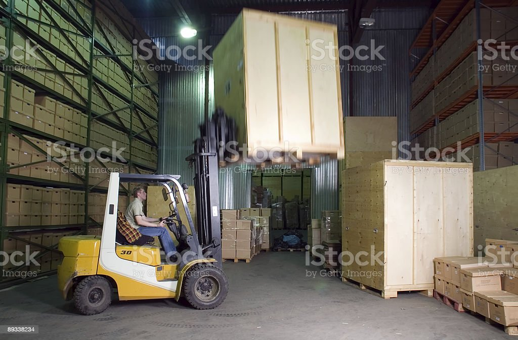 Warehouse worker using a forklift to lift wooden wardrobes stock photo