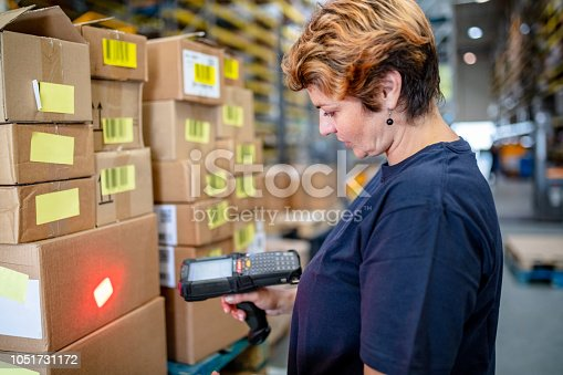 istock Warehouse worker using bar code scanner on box in warehouse 1051731172