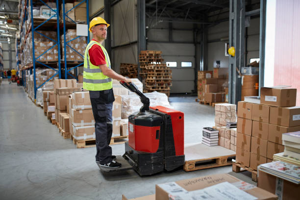 Warehouse worker walking among shelves with handcart Male worker distributing cardboard boxes in a warehouse pallet jack stock pictures, royalty-free photos & images