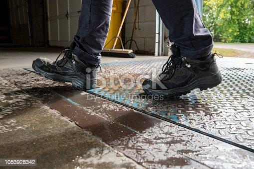 Warehouse worker walking on a wet tread plate on a loading dock