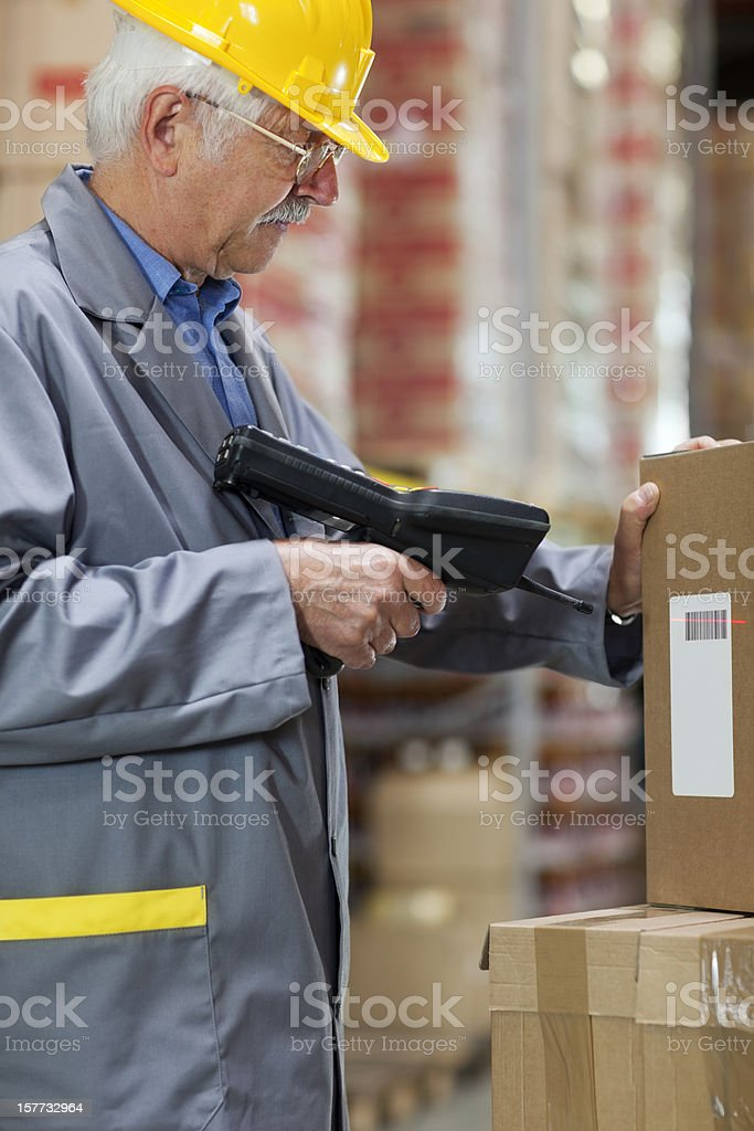 warehouse  worker, warehouseman scanning cardboard box with bar code reade royalty-free stock photo