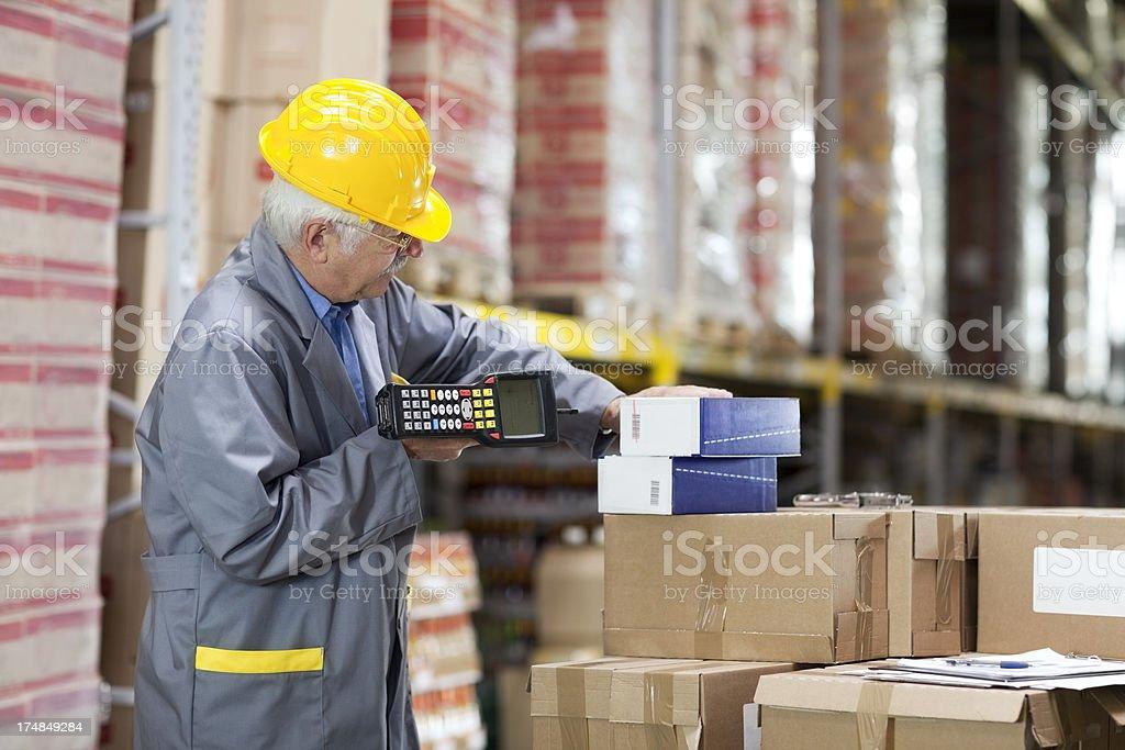 warehouse  worker, warehouseman scanning cardboard box with bar code reade. royalty-free stock photo