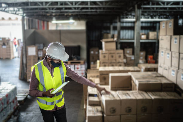 Warehouse worker wearing face mask and protective workwear checking products using digital tablet stock photo