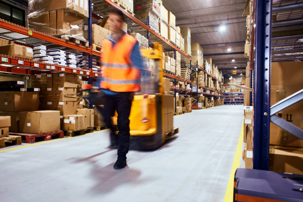 warehouse, worker with a forklift in motion blur. - logistica foto e immagini stock