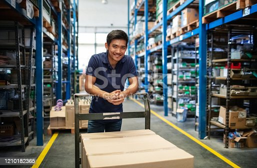 Male worker standing with a trolley with boxes in warehouse. Warehouse worker in uniform with a cart in aisle of storage racks.