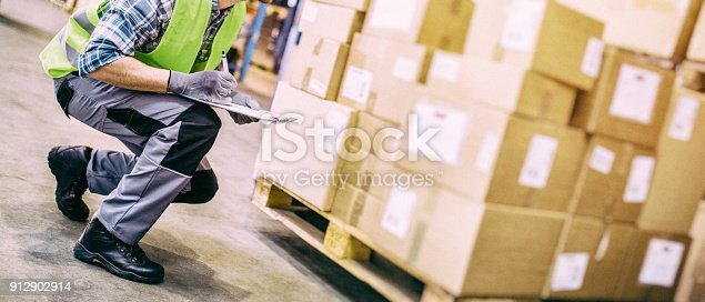 Side view of a postal worker with a hardhat bending over to inspect packages.