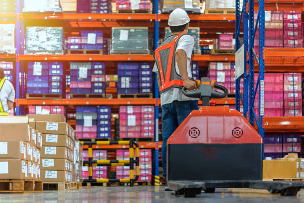 Warehouse Worker with Hand Truck. Warehouse worker walking among shelves with hand truck in to large storage room. pallet jack stock pictures, royalty-free photos & images
