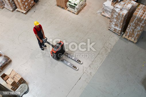 Male worker distributing cardboard boxes in a warehouse