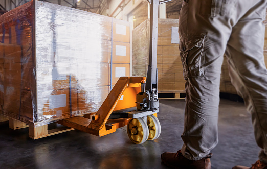 Warehouse worker working with hand pallet jack unloading cargo boxes at the warehouse storage. shipment boxes.