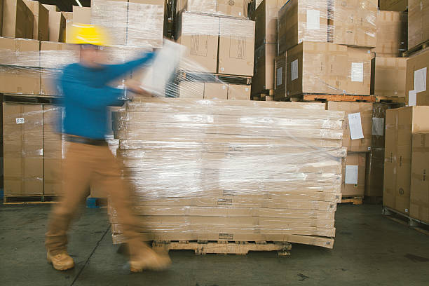 warehouse worker wrapping boxes stock photo