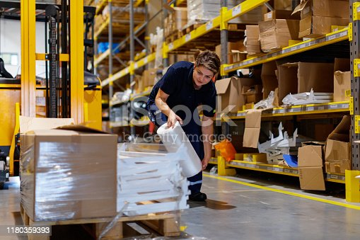 Female warehouse worker wrapping palletes for shipment