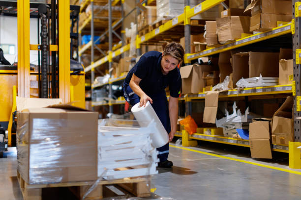 Warehouse worker wrapping palletes for shipment stock photo