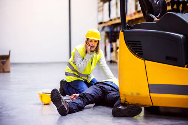 Warehouse workers after an accident in a warehouse. An accident in a warehouse. Woman with smartphone and her colleague lying on the floor next to a forklift. crash stock pictures, royalty-free photos & images