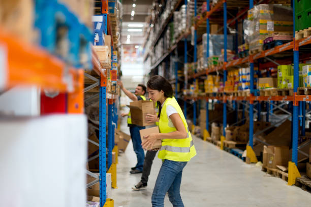 Warehouse workers are stacking goods onto the shelves stock photo