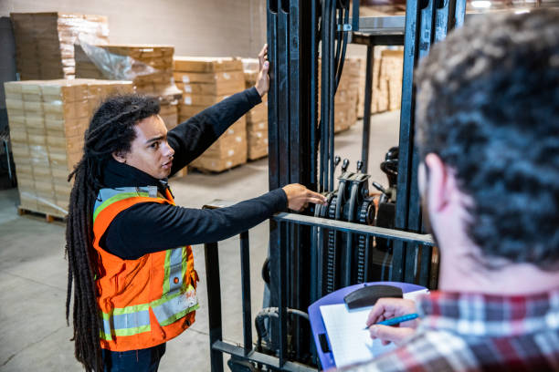 Warehouse workers carrying out a pre-shift safety check on a forklift. stock photo