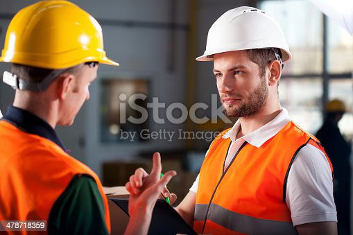 Two warehouse workers discussing about new project