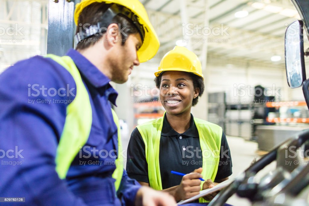 Warehouse workers discussing shipping schedule stock photo