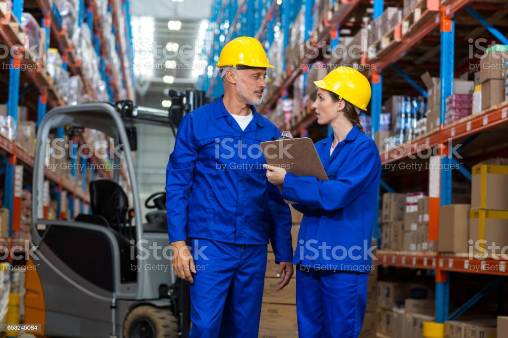 Warehouse workers discussing with clipboard stock photo