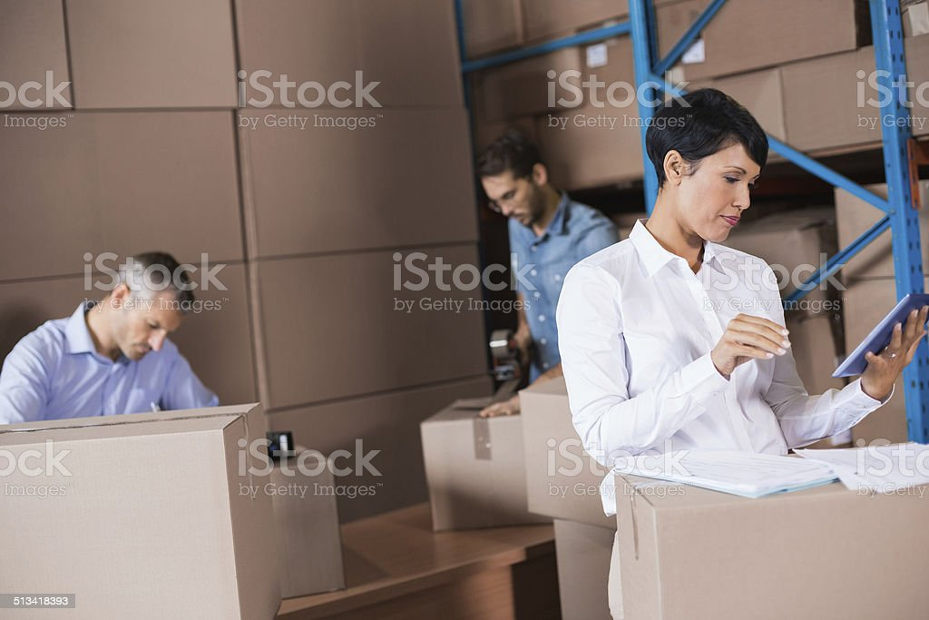 Warehouse workers preparing a shipment Warehouse workers preparing a shipment in a large warehouse 20-29 Years Stock Photo