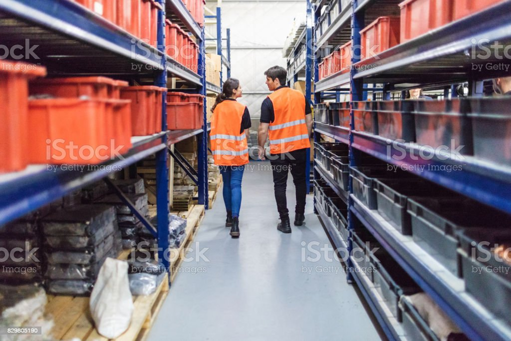 Rear view of two warehouse workers waking through aisle in store...