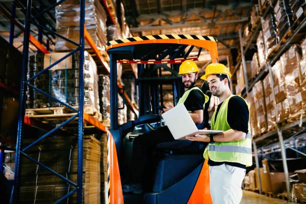 magazijnmedewerkers die samenwerken met vorkheftrucks - warehouse worker stockfoto's en -beelden