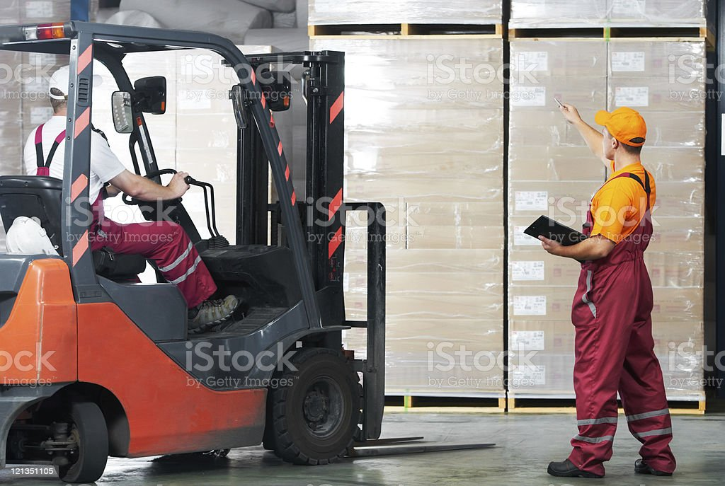 warehouse works (forklift and workers) stock photo