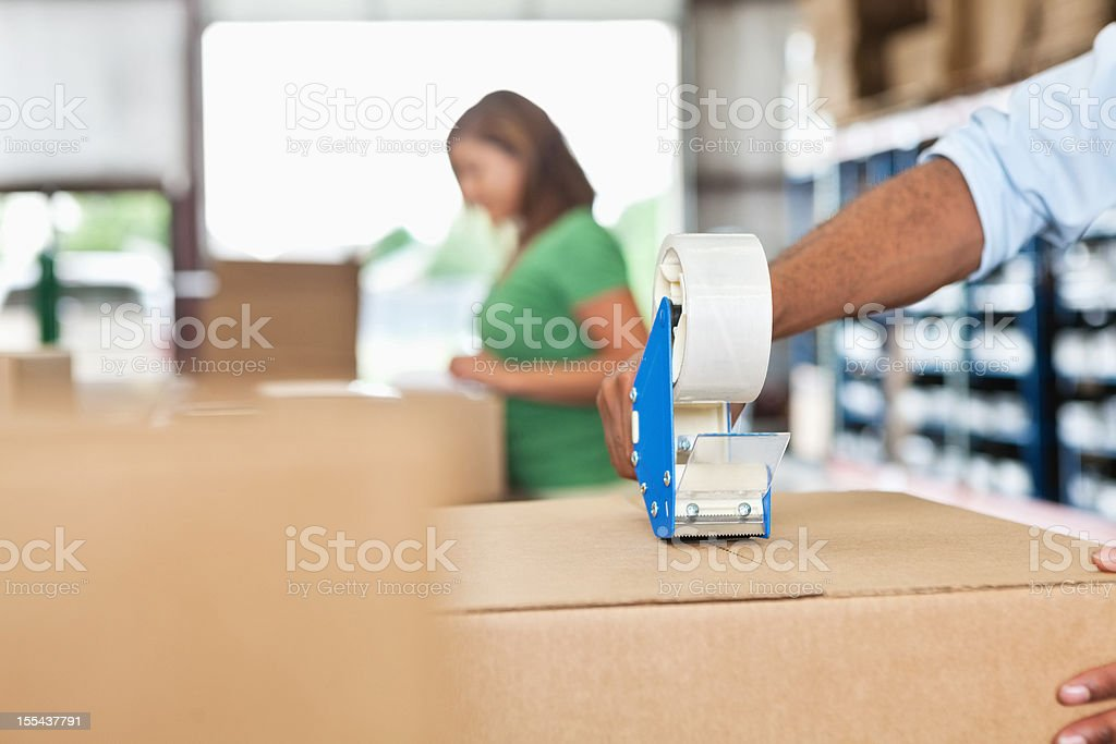 Warhouse worker assembling package close up on tape dispenser stock photo