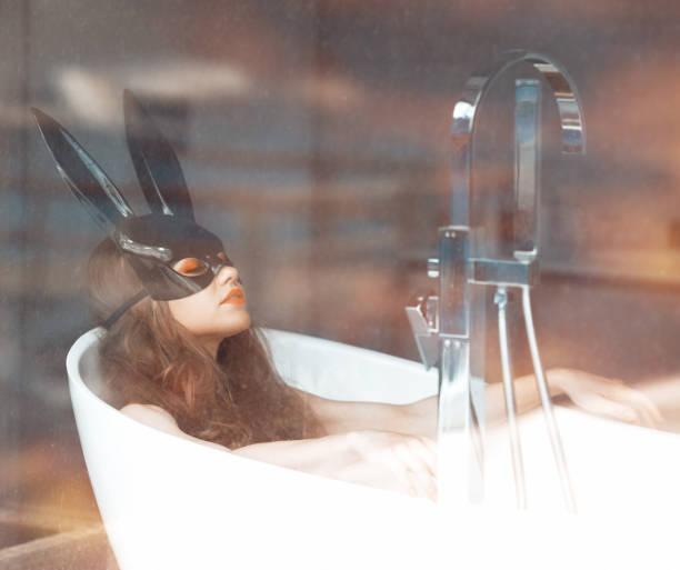 Waring bunny mask while taking a bath stock photo
