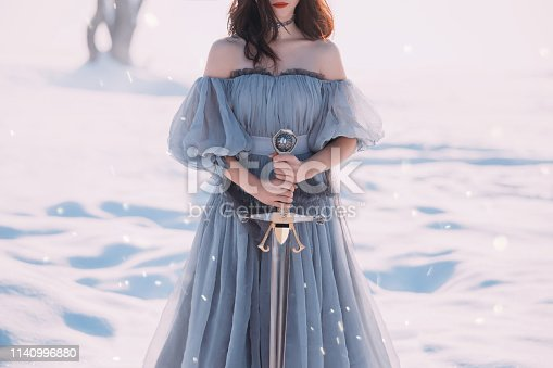 warlike girl with dark hair in long gray vintage light dress, lady of cold and frost, bare open shoulders and sharp silver sword in hands, goddess of death with red lips, character for computer games.