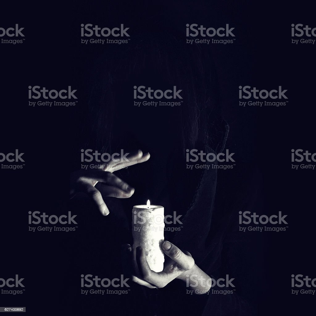 Warlock holds hands over burning candle in darkness stock photo