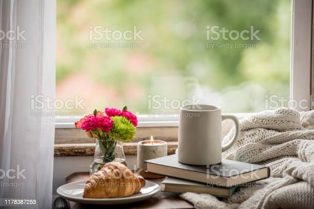 Photo of Warm and cozy at home reading a book and drinking coffee