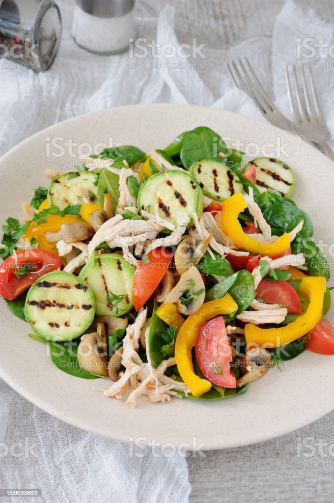 Warm chicken salad with spinach, tomato slices, sweet pepper, grilled zucchini, and champignons, all dressed with herbs and fragrant oil. stock photo