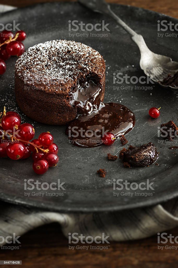 Warm Chocolate Lava Cake with Molten Center and Red Currants stock photo