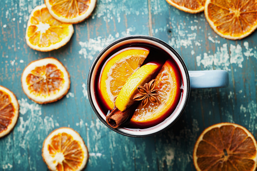 Warm christmas mulled wine or gluhwein with spices and orange slices on wooden teal table top view. Traditional drink on winter holiday.