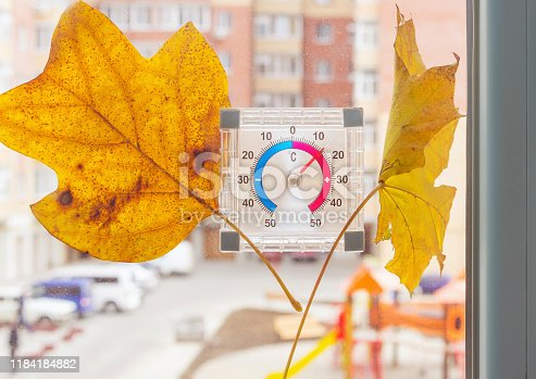 istock Warm cloudy fall day, weather in autumn. Thermometer with yellow fallen leaves at home window. 1184184882