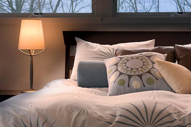 warme, moderne schlafzimmer - nachttischleuchte stock-fotos und bilder